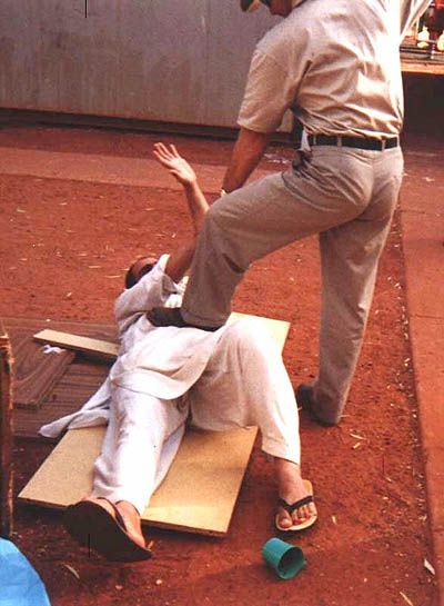 A guard puts his boot on a detainee at the Curtin detention centre