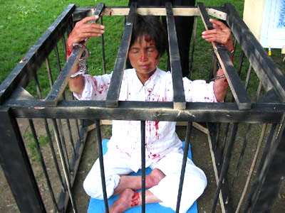 A Chinese Falun Gong 'dissident' caged, handcuffed and bleeding