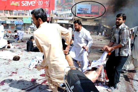 People clean up the bodies after a suicide bomber attack on a rally in Quetta